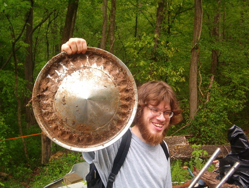 Michael Pollock holding up a hub cap during an Earth Day clean up in 2006